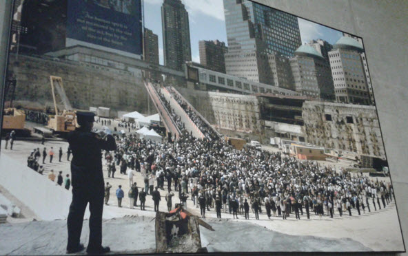 A police officer plays Taps in The Pit at the WTC's Ground Zero on the 1st anniversary of 9/11.